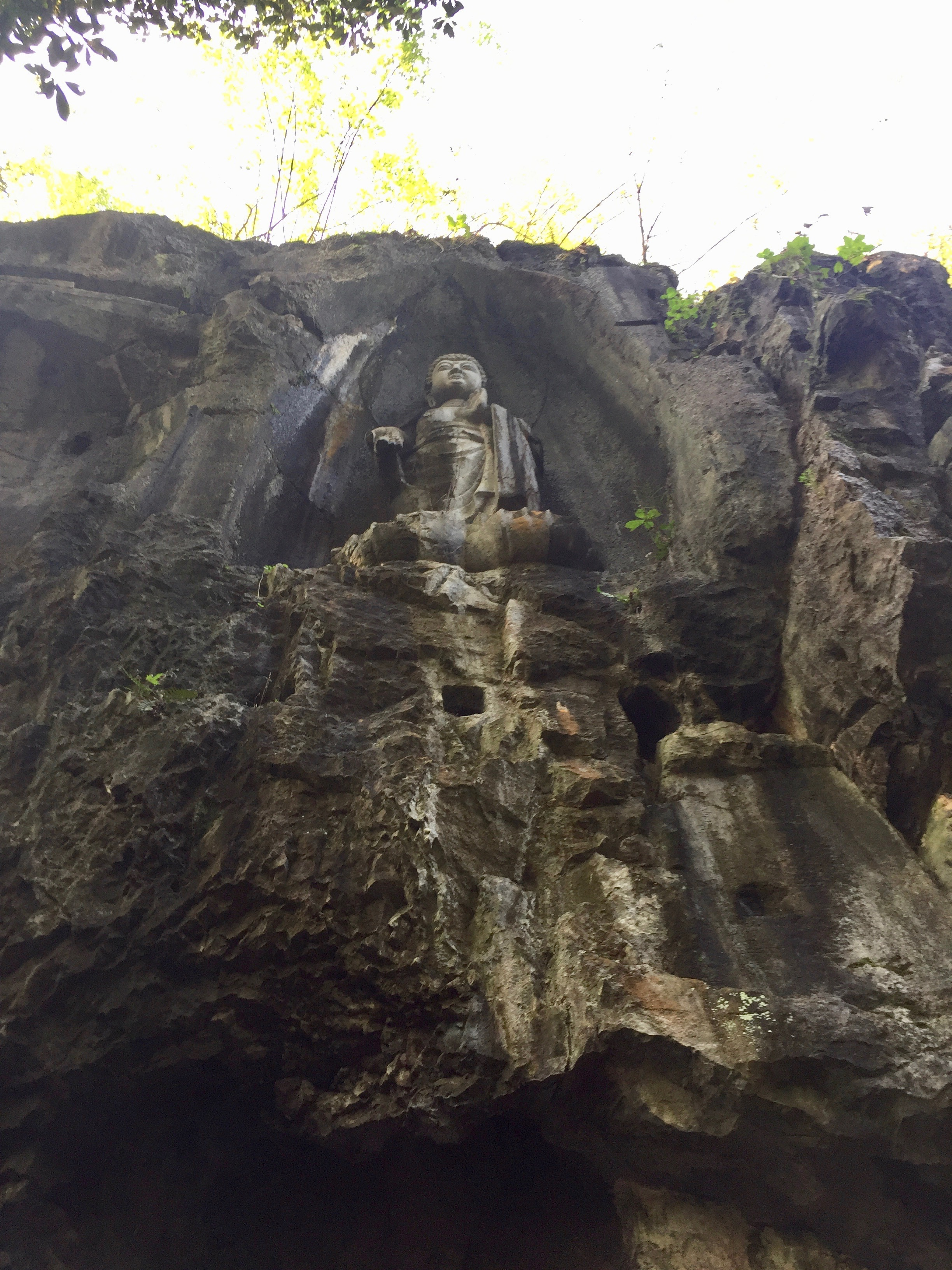 An ancient Buddha sits atop the entryway to Lingyin Temple (Hangzhou, China)