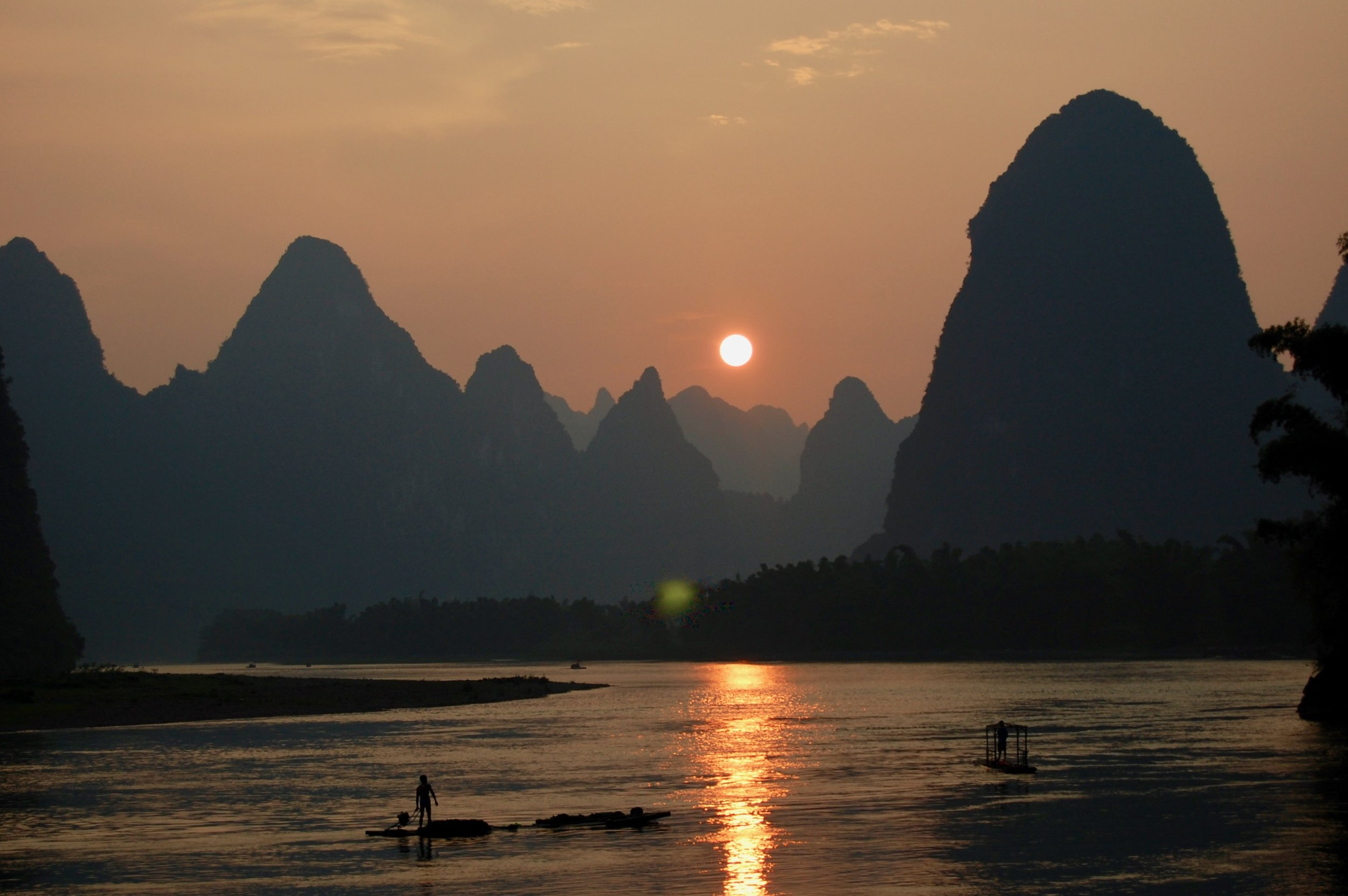 A fisherman plies his trade as another day draws to a close on the Li River. The view from this exact location is featured on the back side of the 20 yuan note (Yangshuo, China)
