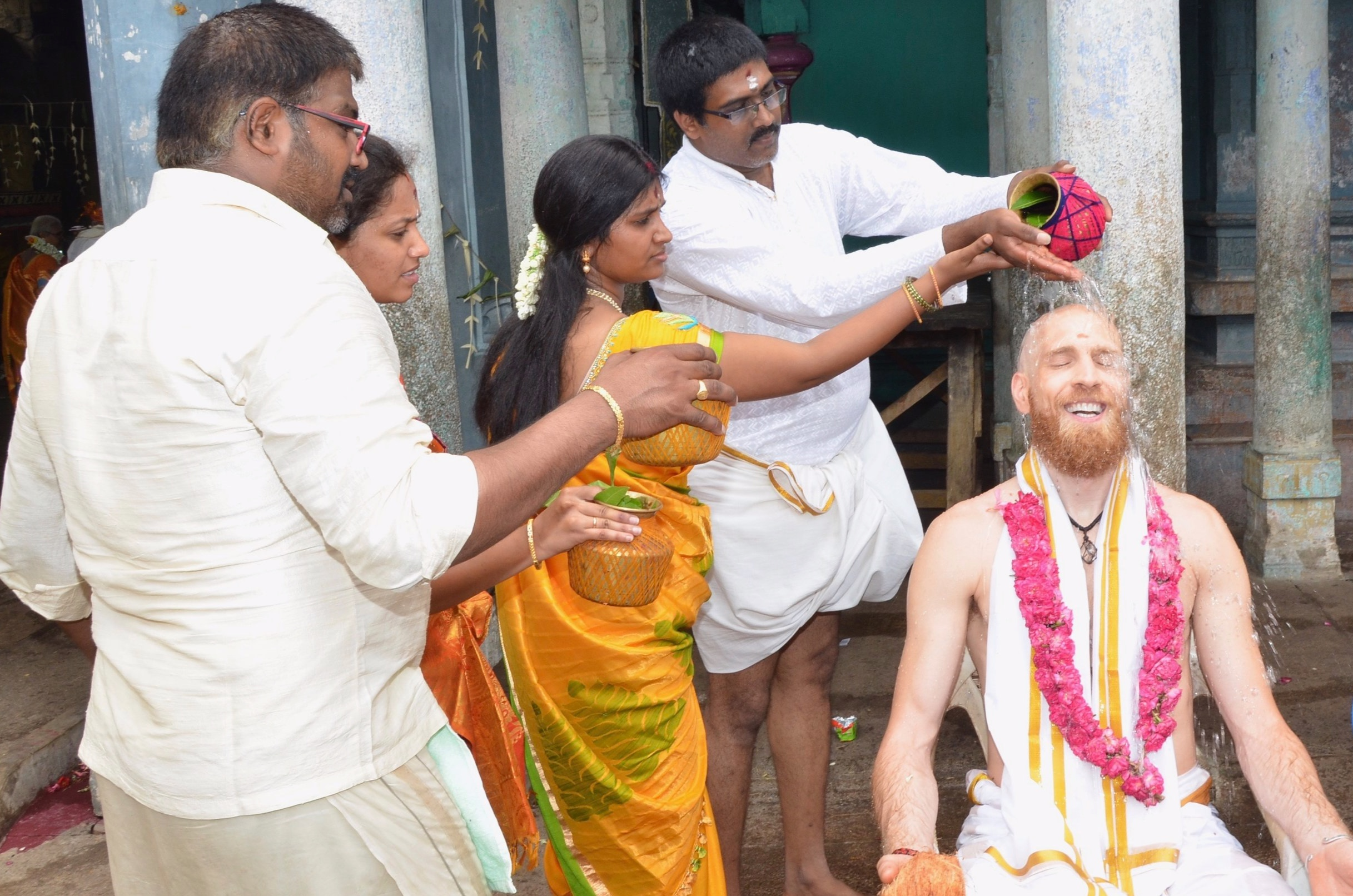 Bathing in love and devotion as fellow pilgrims seal the blessing power of the puja with water offerings (Thirukkadaiyur, Tamil Nadu)  Photo credit: unknown