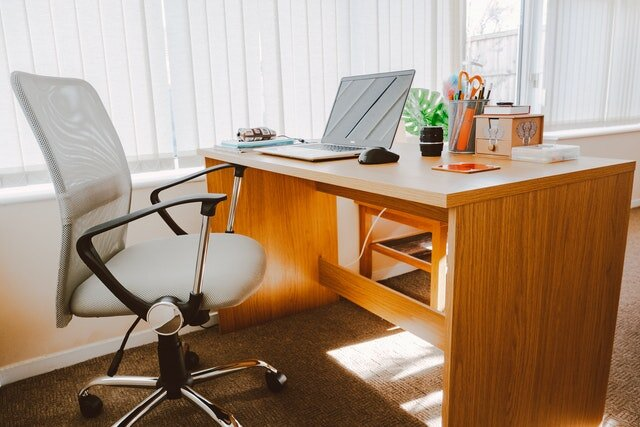 home office chair wooden desk warm natural light inviting computer pens plants.jpg