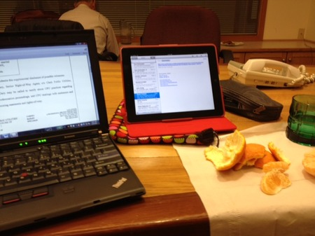 Photo: At a break in the deposition, eating a sumo orange (highly recommend these). Ipad has joined laptop - they are a good team. N in the background.