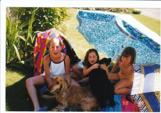 Photo: The girls at ages 8, 6 and 3 (with their dogs Coco and Tucker) still remember hanging out on the front lawn that summer.
