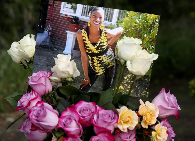 After her slaying, a photo of Charleena Lyles and flowers were left outside the apartment building where she had lived in Solid Ground's Sand Point housing campus. (Ken Lambert/The Seattle Times)