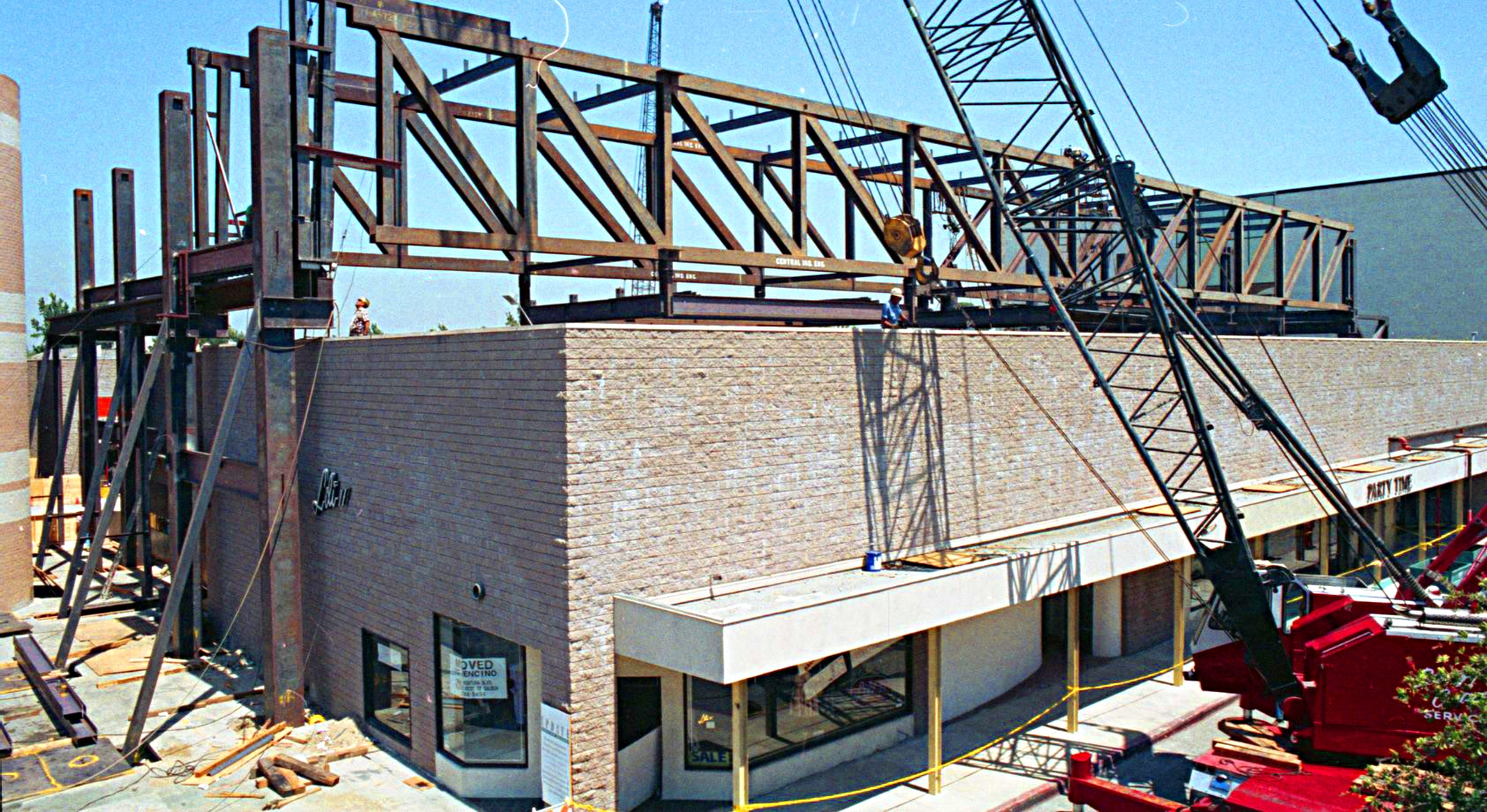 - Construction photo showings the installation of long span trusses over existing tenant buildings
