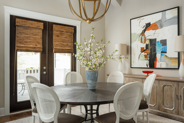 In this Chattanooga dining room, we combined traditional French Louis chairs with modern art and a contemporary light fixture. More contrast is provided between the rough texture of the bamboo shades and metallic accents on the slick white and gold lamps. OH, and that's a vintage carnival glass compote on the contemporary buffet!