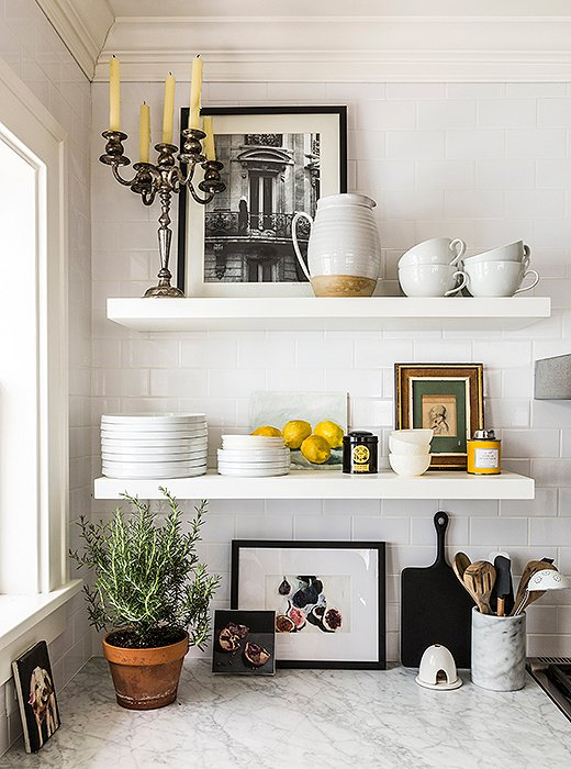 An eclectic mix of framed art was tucked into these open shelves and mixed with more utilitarian elements - including a big pot of rosemary! Image from OneKingsLane.