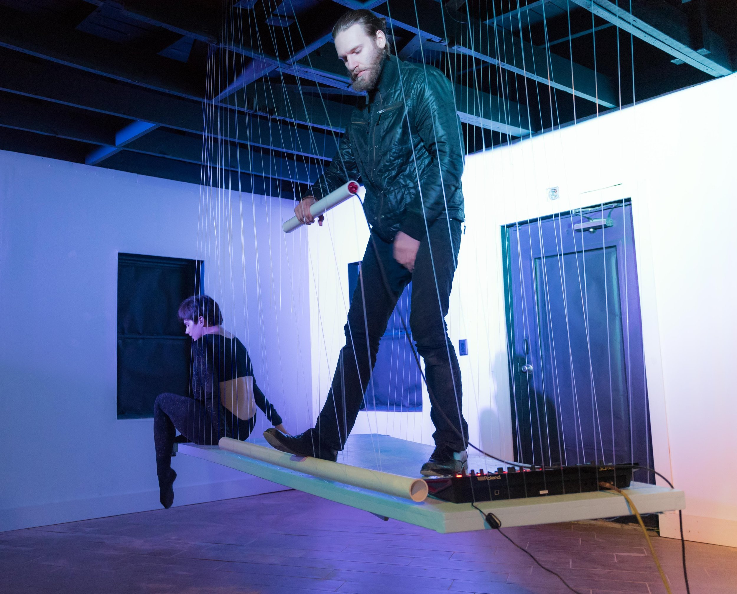 Prism2 - Floating platform suspended by harp string. Lights, performance live sound in vacant structure.