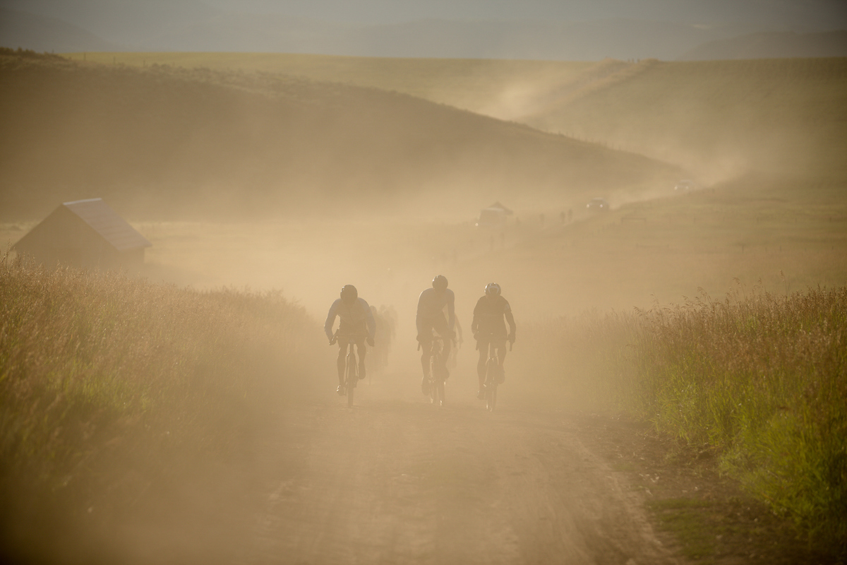 Riders push through a dust cloud kicked up by riders, vehicles and motorcycles on course. PC: Linda Guerratte