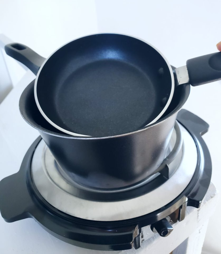 Kristen's personal setup. A small fry pan, over a small saucepan, on an electric burner.