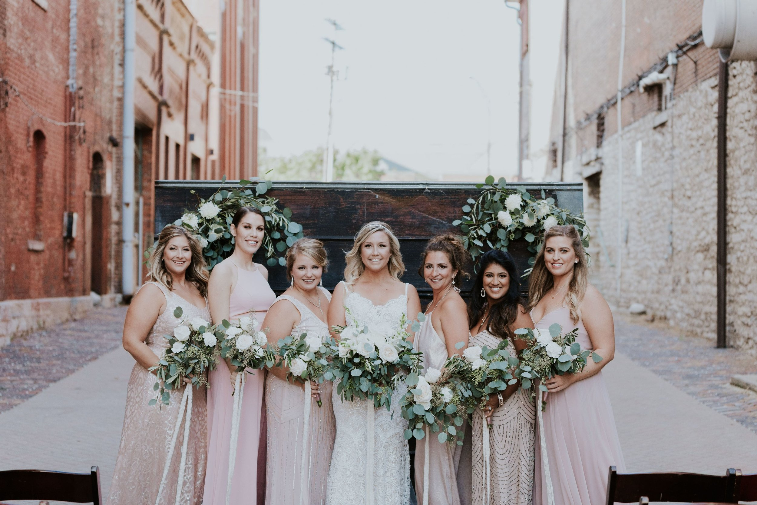 Bride and her bridesmaids in mix and match looks in blush pink and gold beaded gowns