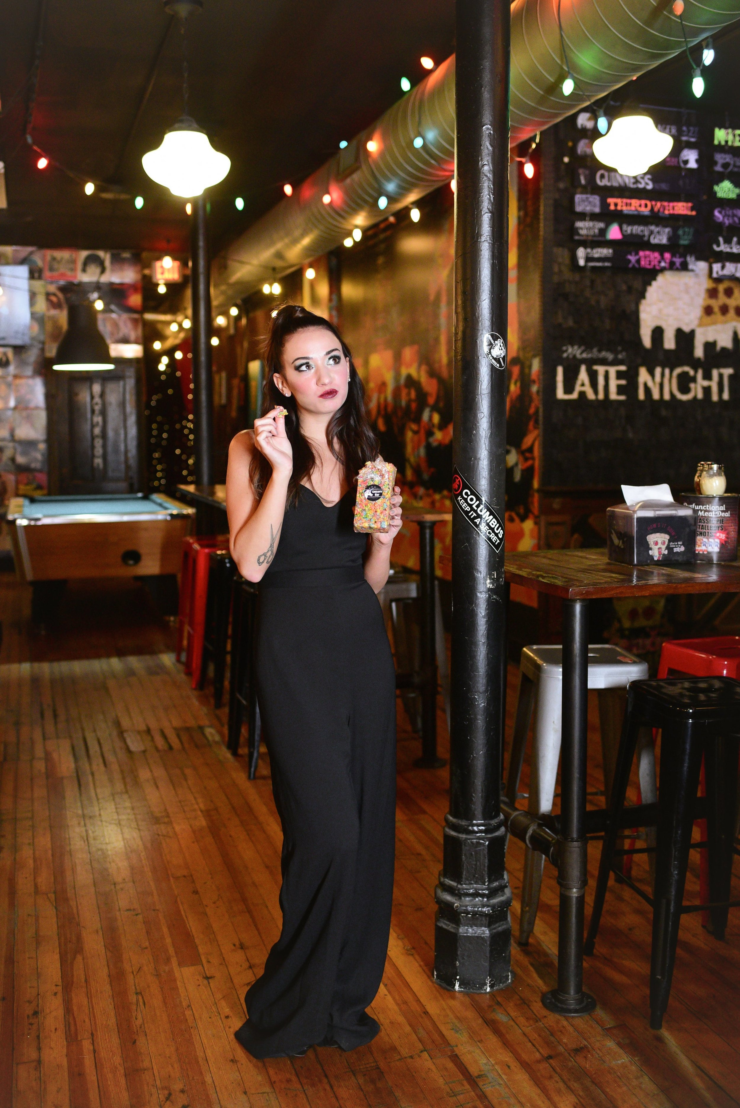 Bridesmaid in Hayley Paige black crepe jumpsuit style 5868 eating Unicorn Bar from Mikey's in Columbus Ohio