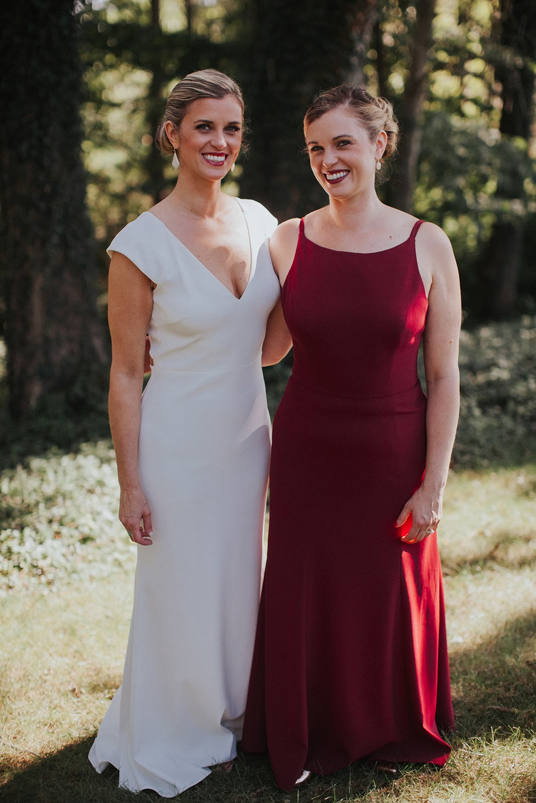 Bride and Bridesmaid wearing Dessy Group Style 6758 in burgundy crepe