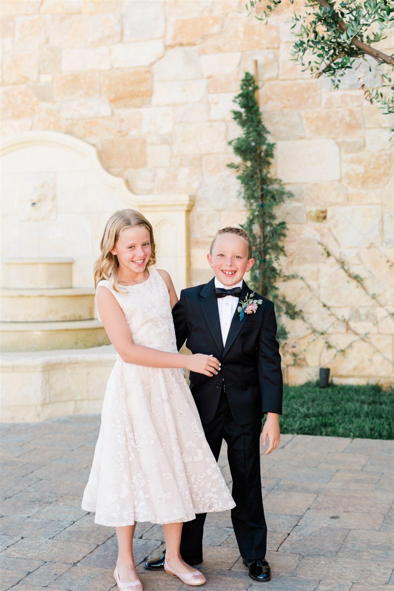 Little girl modeling a white La Petite flower girl gown at Gilded Social