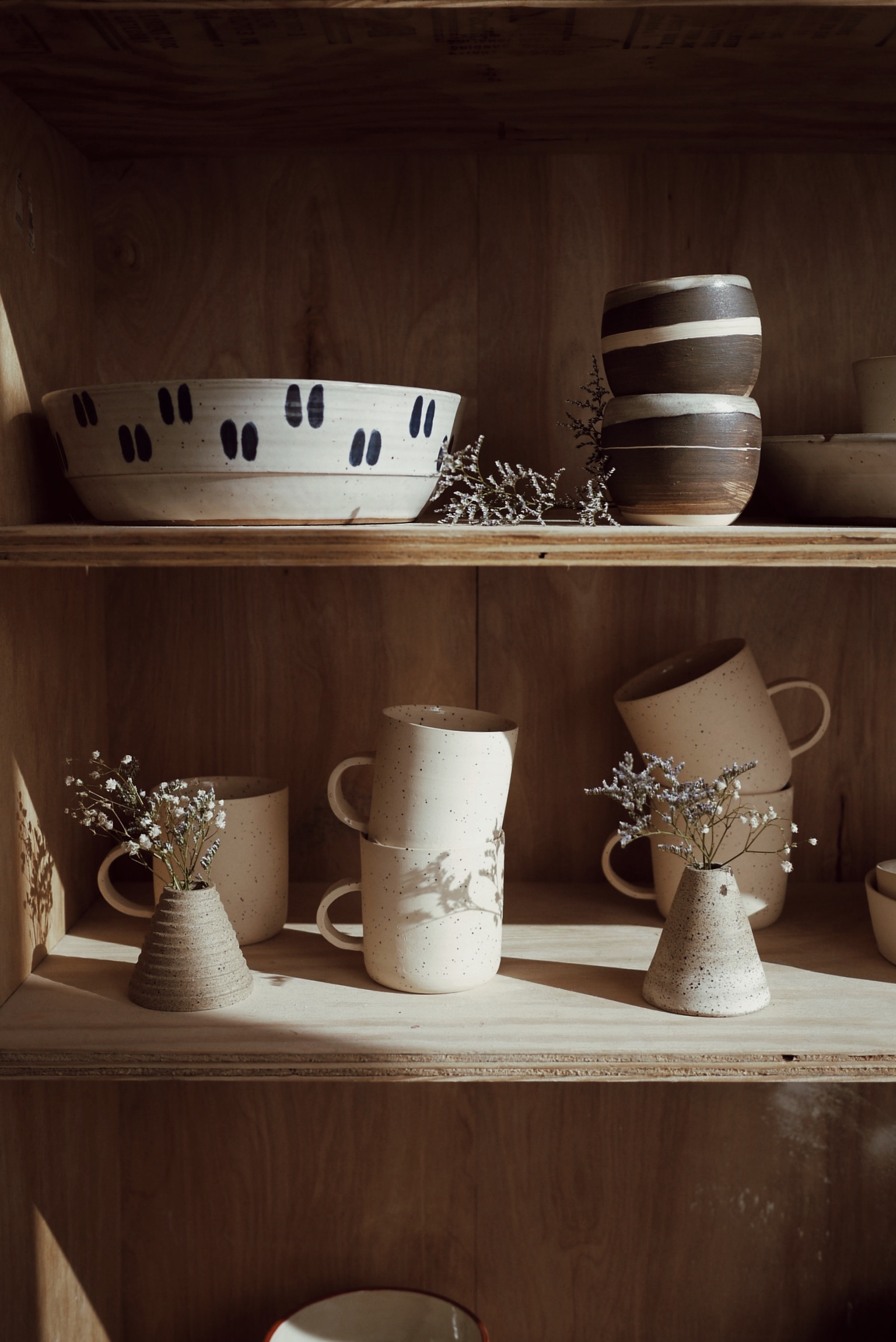 Some dramatic little flowers casting shadows onto my speckled mugs, with more of  Renee 's tableware above.