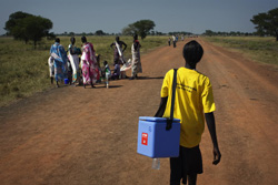 A healthcare worker in South Sudan carrying the typical kind of rural vaccine transport - an insulated cooler.       Credit: UNICEF