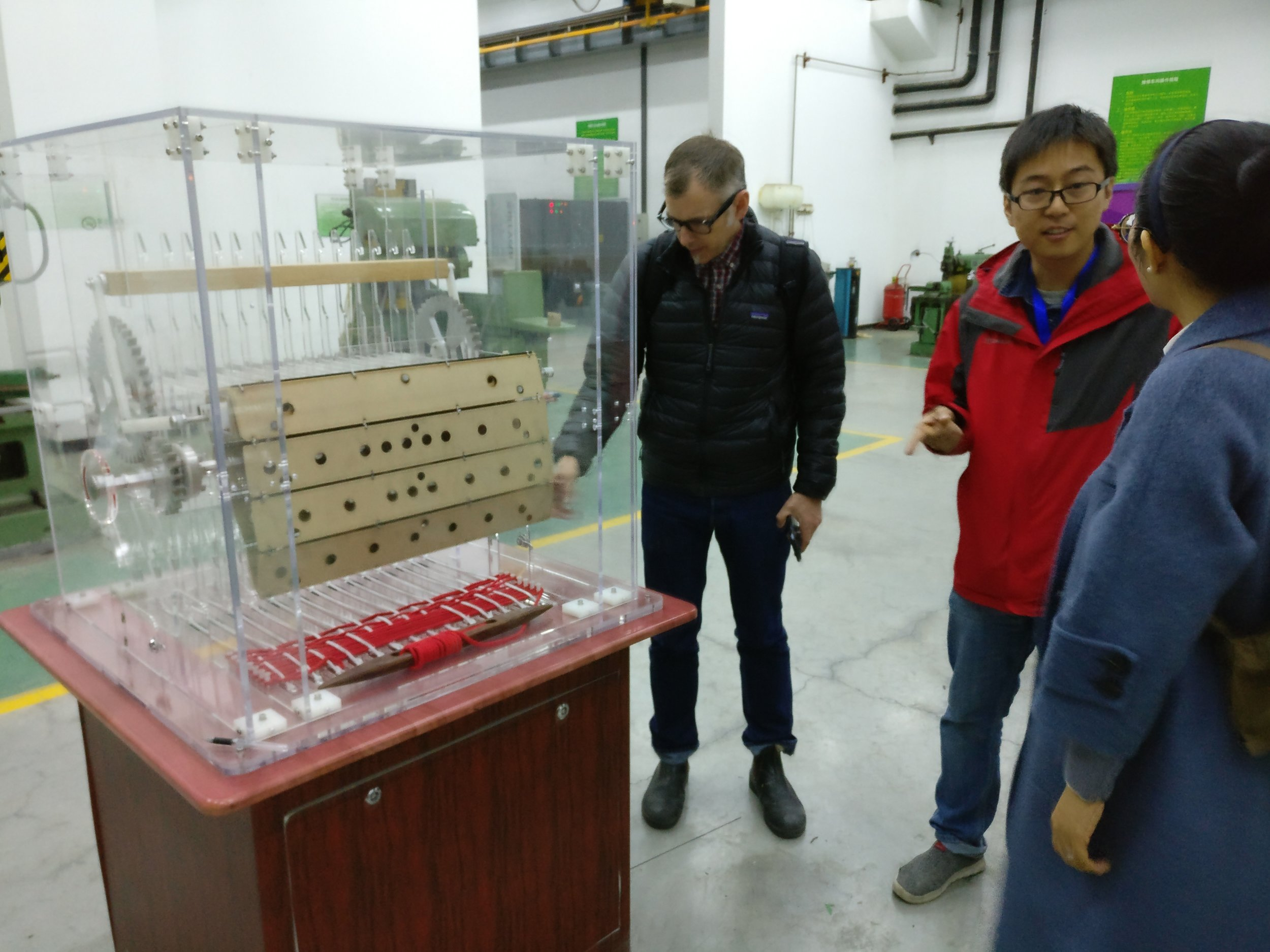 Mr. Eric Dimond from Exploratoriumin is studying a prototype of an interactive knitting machine, created by Mr. Wei Fei at the exhibition production shop at the China Science and Technology Museum.