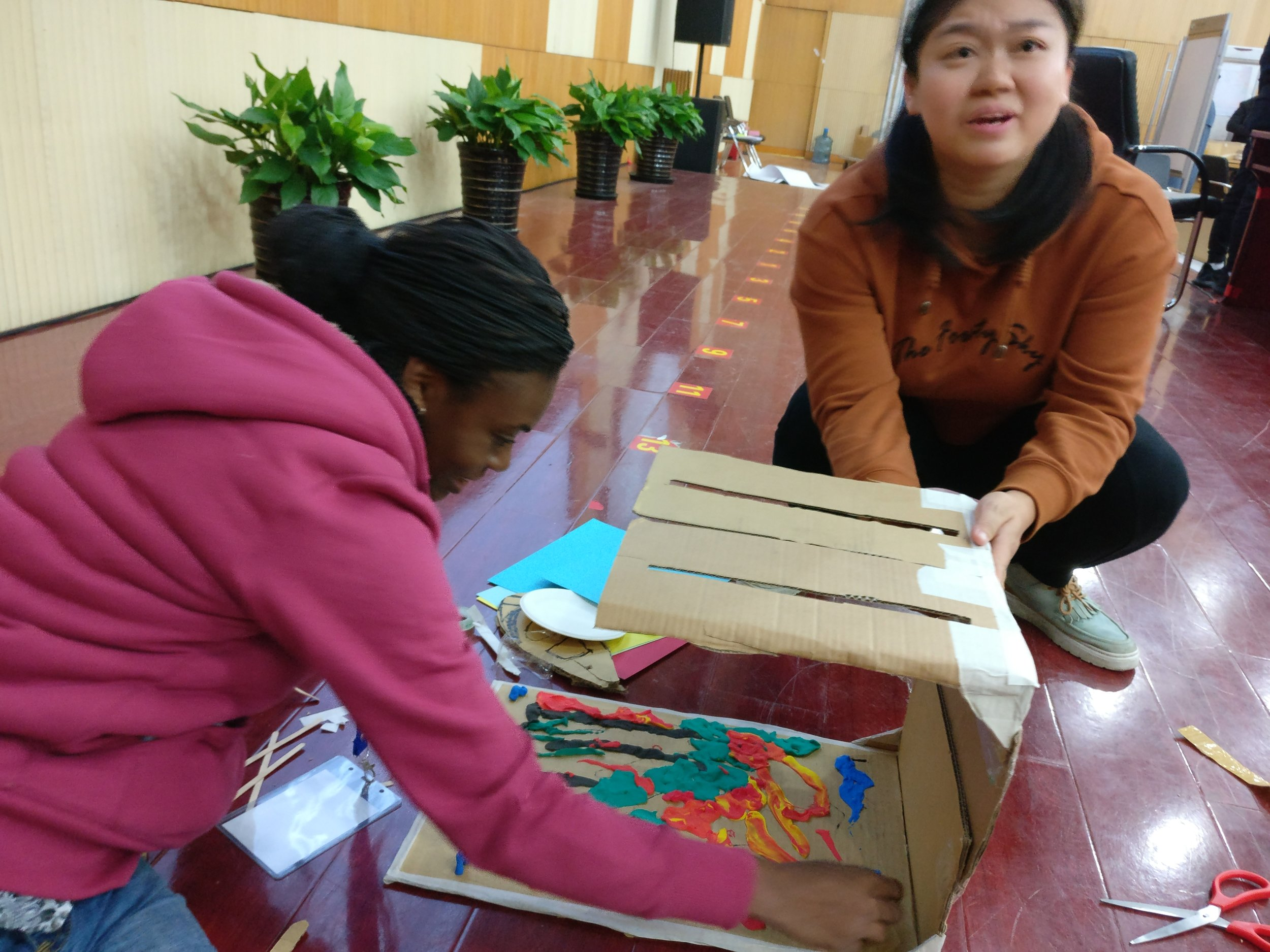 Ruiting Li setting up a prototype for an exhibit about natural catastrophies.