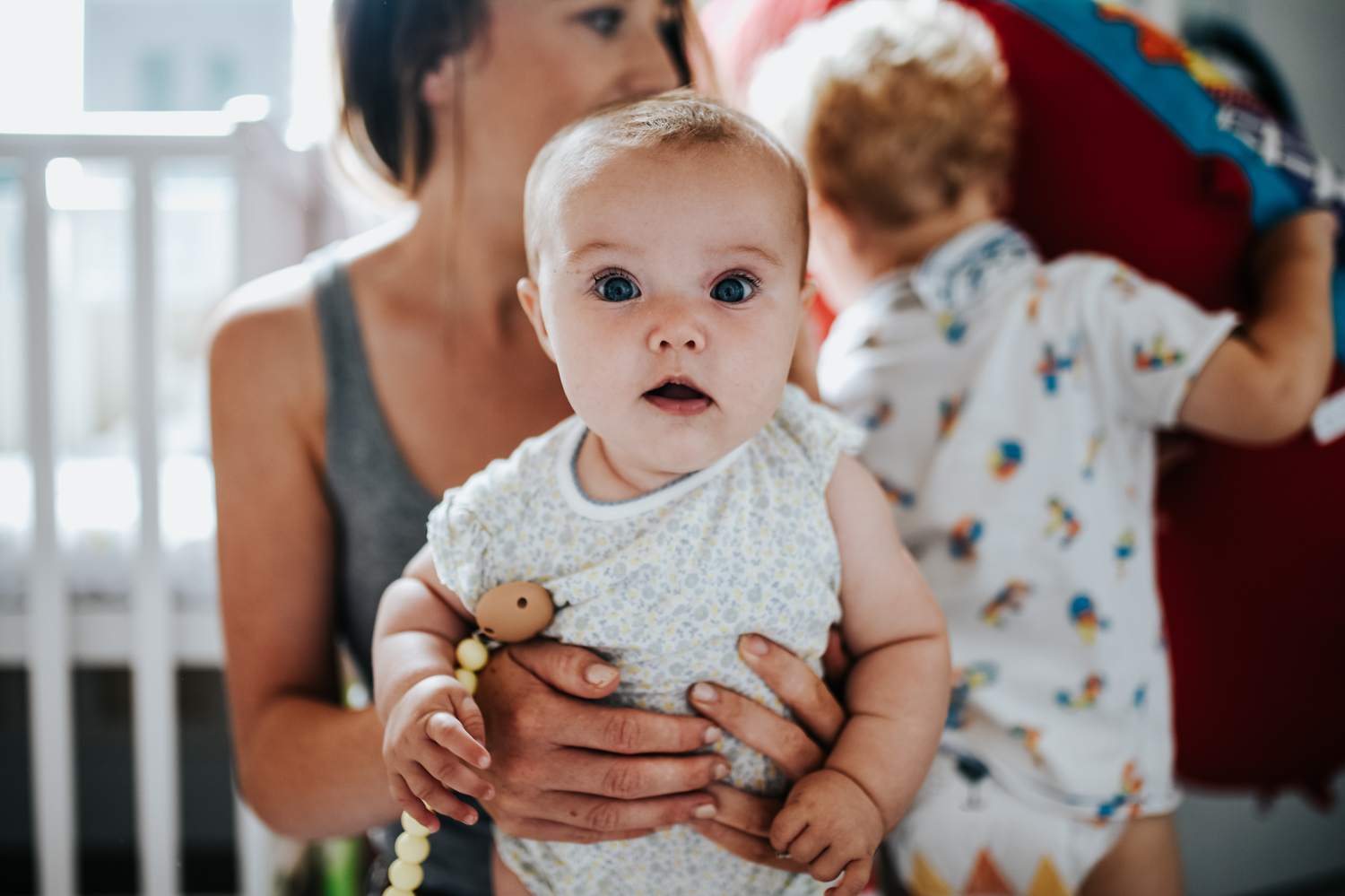 A baby stares directly at the camera as she is being held by her mother as they sit on the floor of their bedroom during this intimate at home photo session in Yeovil, Somerset.