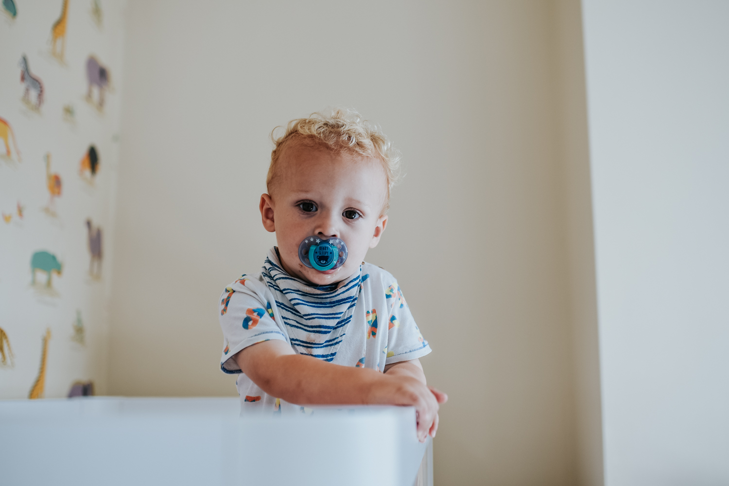 A serene shot of a toddler boy standing in his cot staring directly at the camera during this day in the life photo session in Yeovil, Somerset.