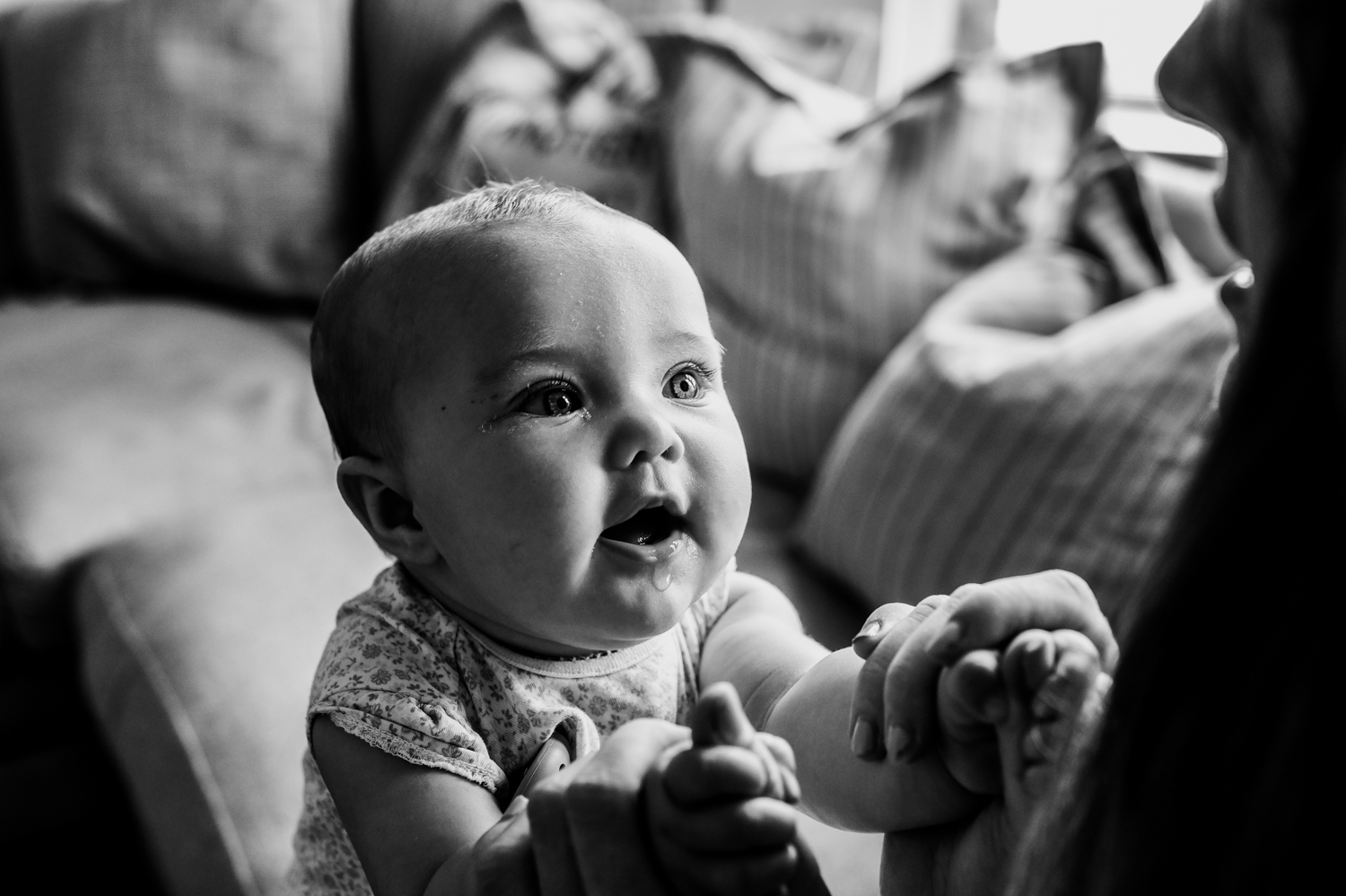 A close up shot of a baby staring at her mother as they hold hands on the sofa during this day in the life photo session in Yeovil, Somerset.