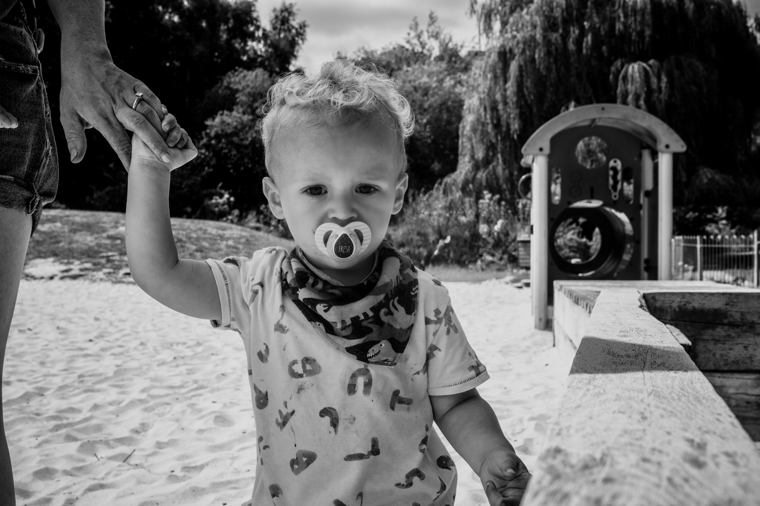 Toddler walks hand in hand with his mother as they walk through the sand pit in their local park during this day in the life family photo session in Yeovil, Somerset.