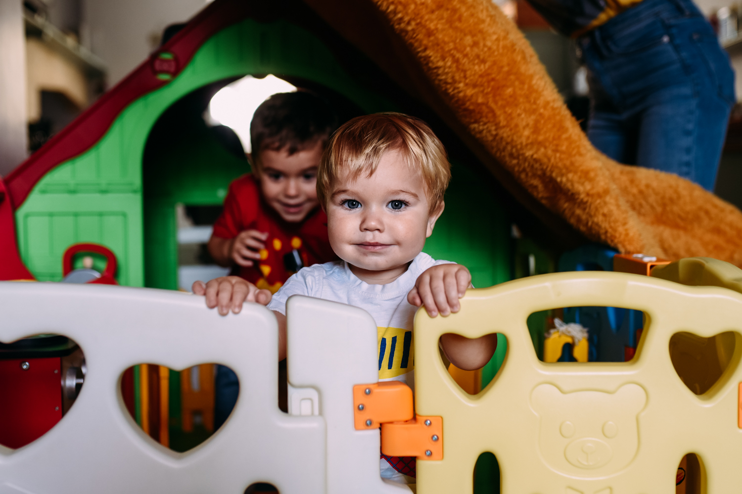 A baby boy stands in his play area in his home smiling directly at the camera during this baby session in Bath.