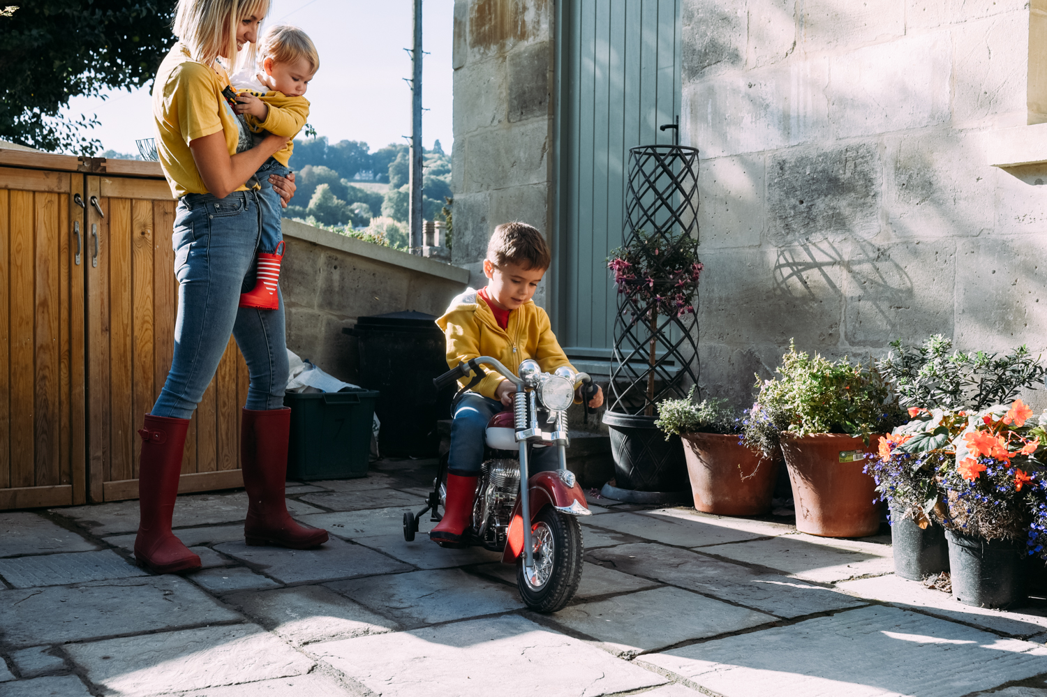 A little boy sits on his miniature motorbike in his garden as his mother and baby brother look on smiling.