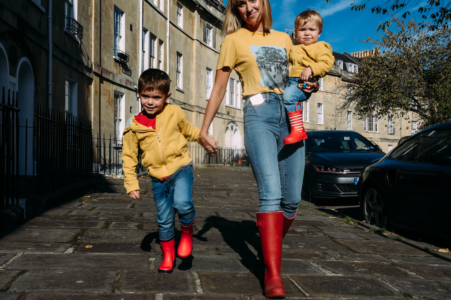 A single mum walks hand in hand with her son as they walk through a pretty crescent during this gorgeous at-home family session in Bath, Somerset.
