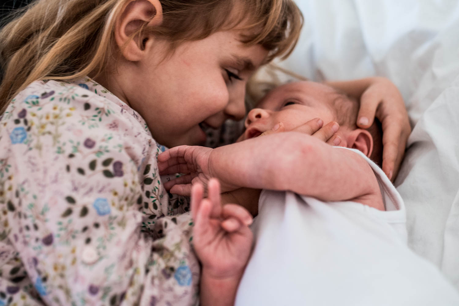A close up shot of a sister cuddling and kissing her newborn baby brother as they lie on a bed together during this documentary family photography session.
