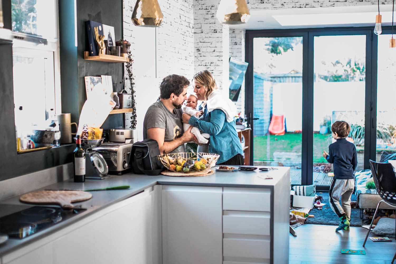 A couple stand in their kitchen as the mother passes their newborn baby to his father during this documentary family photography session in Bristol.