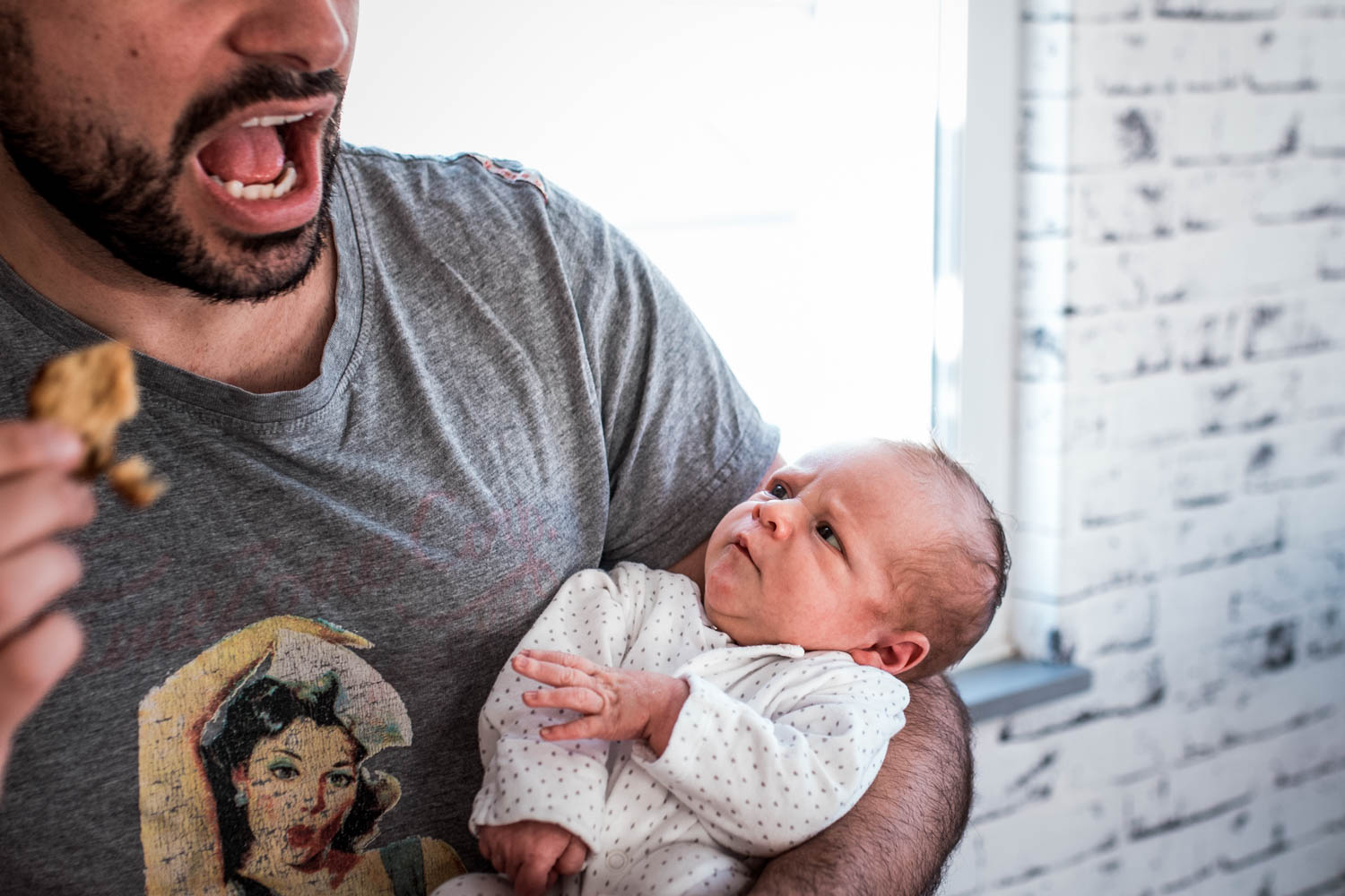 A father holds his newborn son in his arms and his son looks up at him during this at-home family photo session in Bristol.