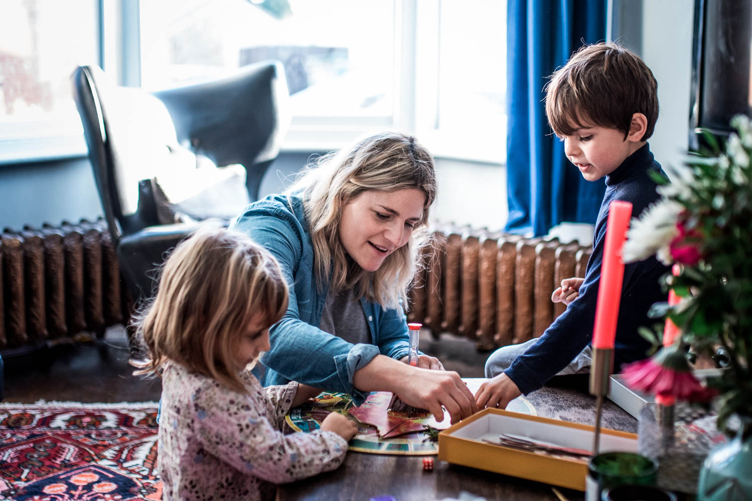 A mother sits on the floor with her children in their living room playing a board game during this relaxed family photo shoot in Bristol.