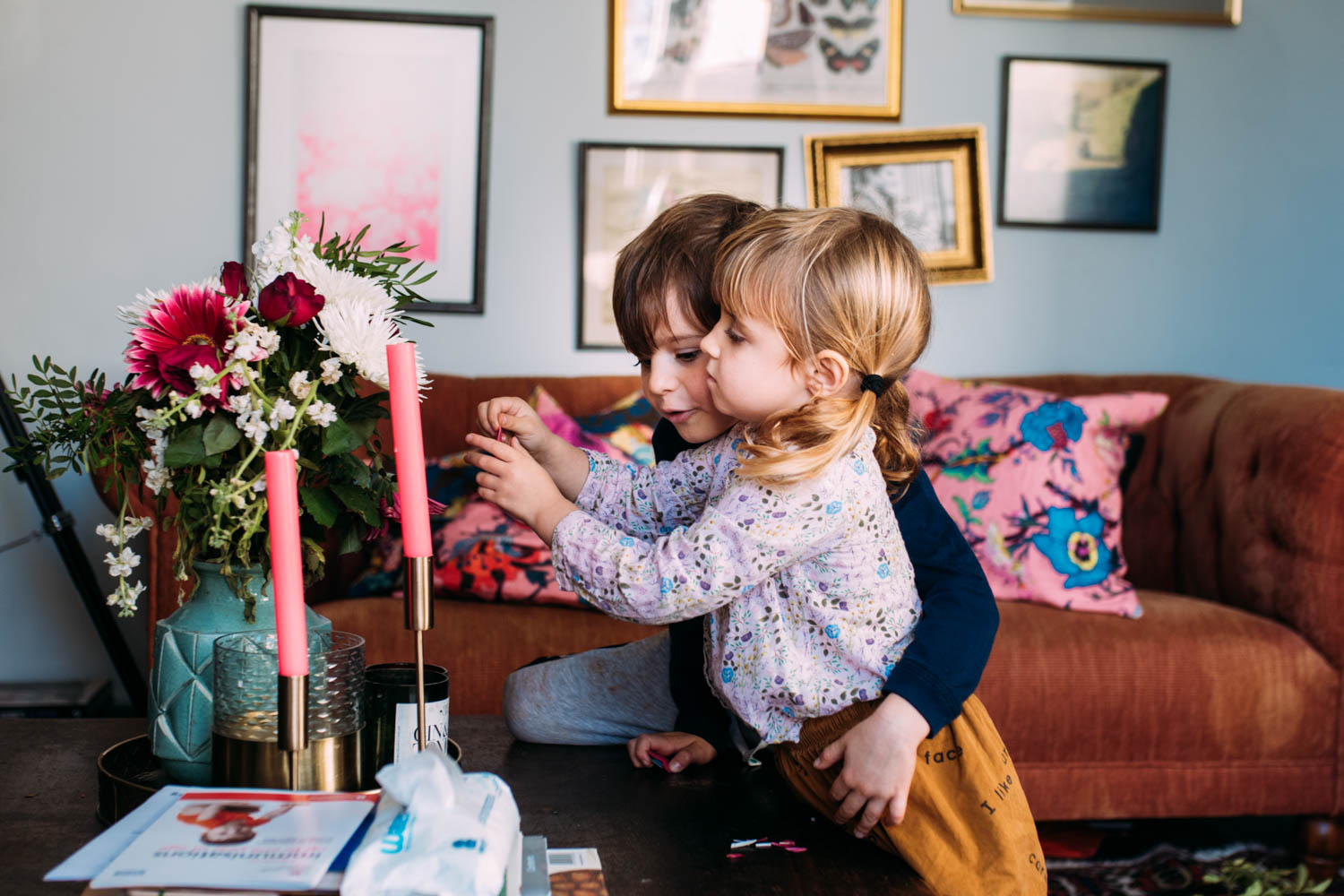 A young brother and sister stand in their living room looking at a bouquet of flowers with their arms round eachother.
