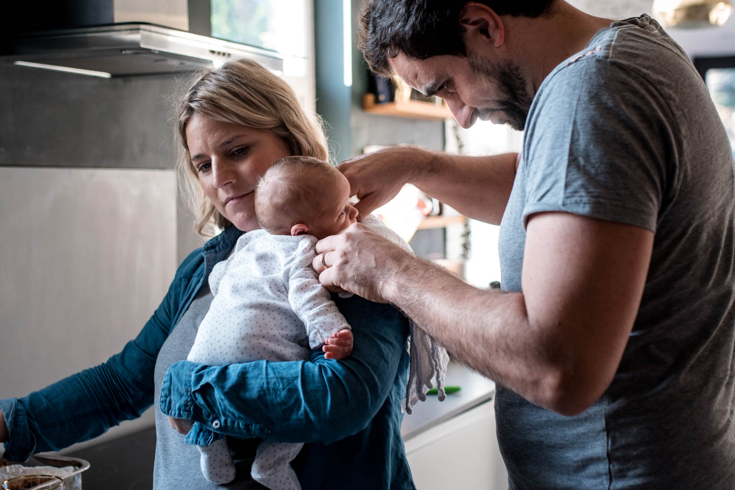 A mother stands in her kitchen and holds her newborn over her shoulder as her husband stands next to her stroking their babies cheek during this documentary family photography session in Bristol.