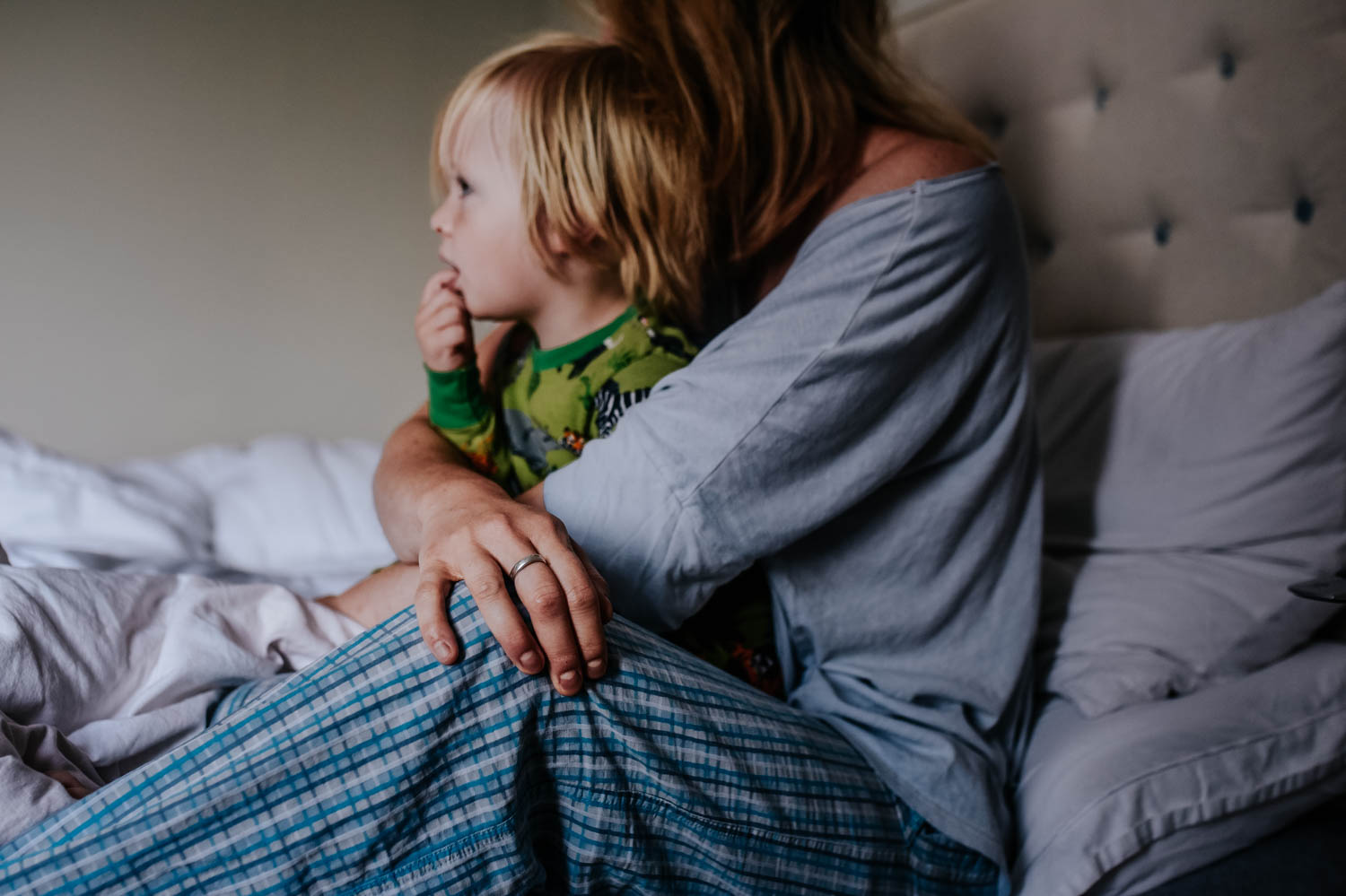 A mother sits in bed with her son on her lap aftee they have just woken up.