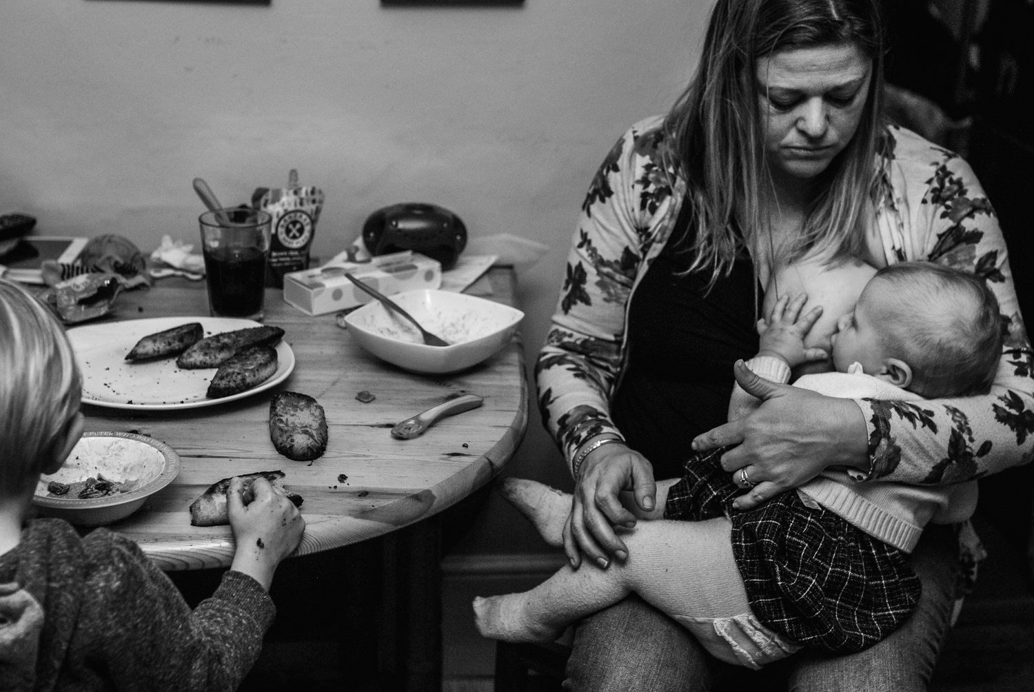 A mother sits and breastfeeds her daughter at the dinner table as she sits with her family to have dinner.
