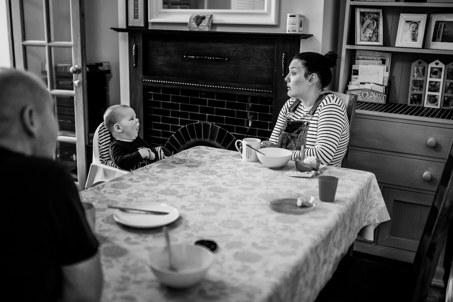 Family sit down at the table having breakfast and the baby yawns at the mother who makes a funny face back during their Day in The Life session in Bristol.