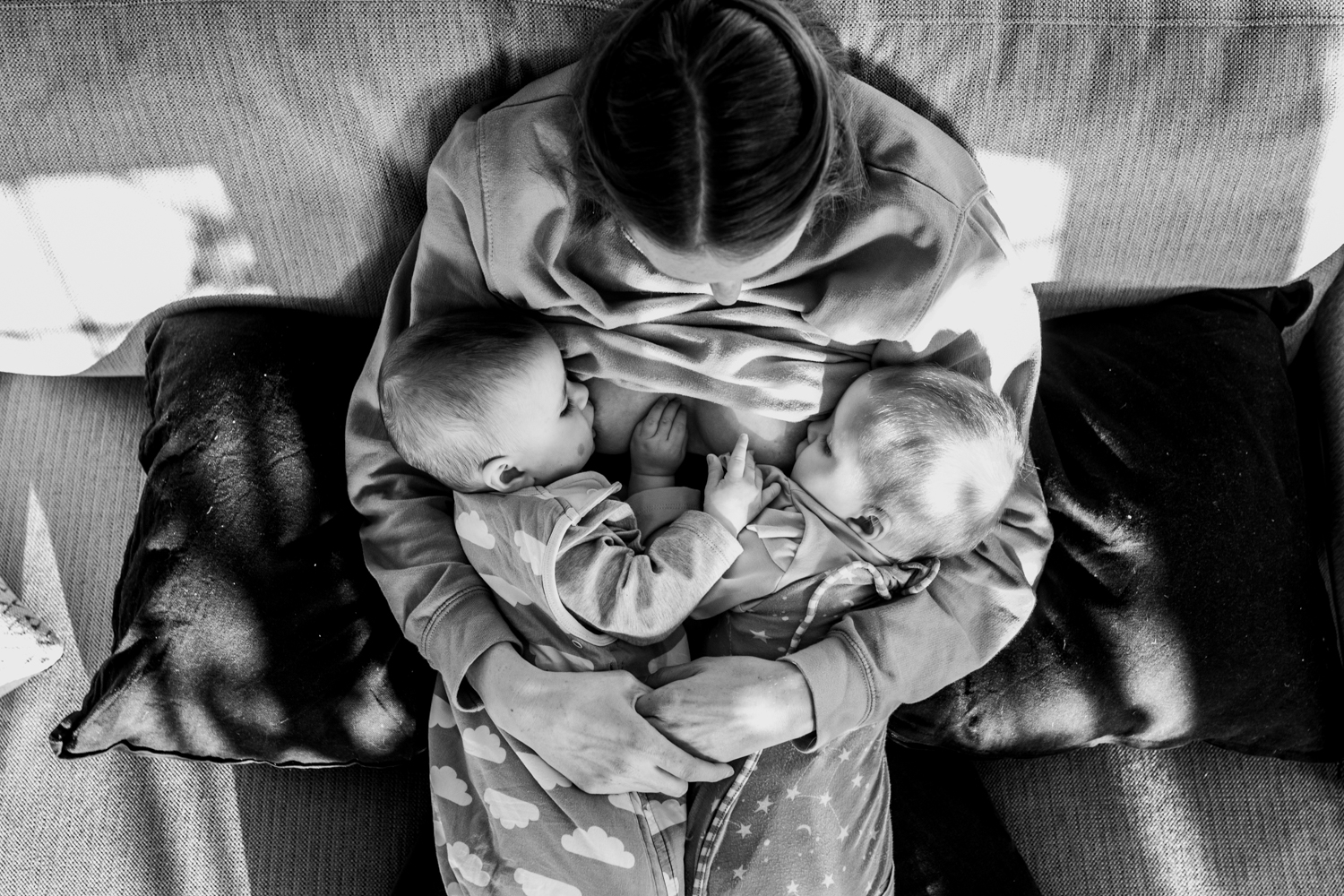 An aerial shot of a mothering mother sitting on her couch tandem breastfeeding her twin daughters during this intimate documentary family photo session in Sussex.