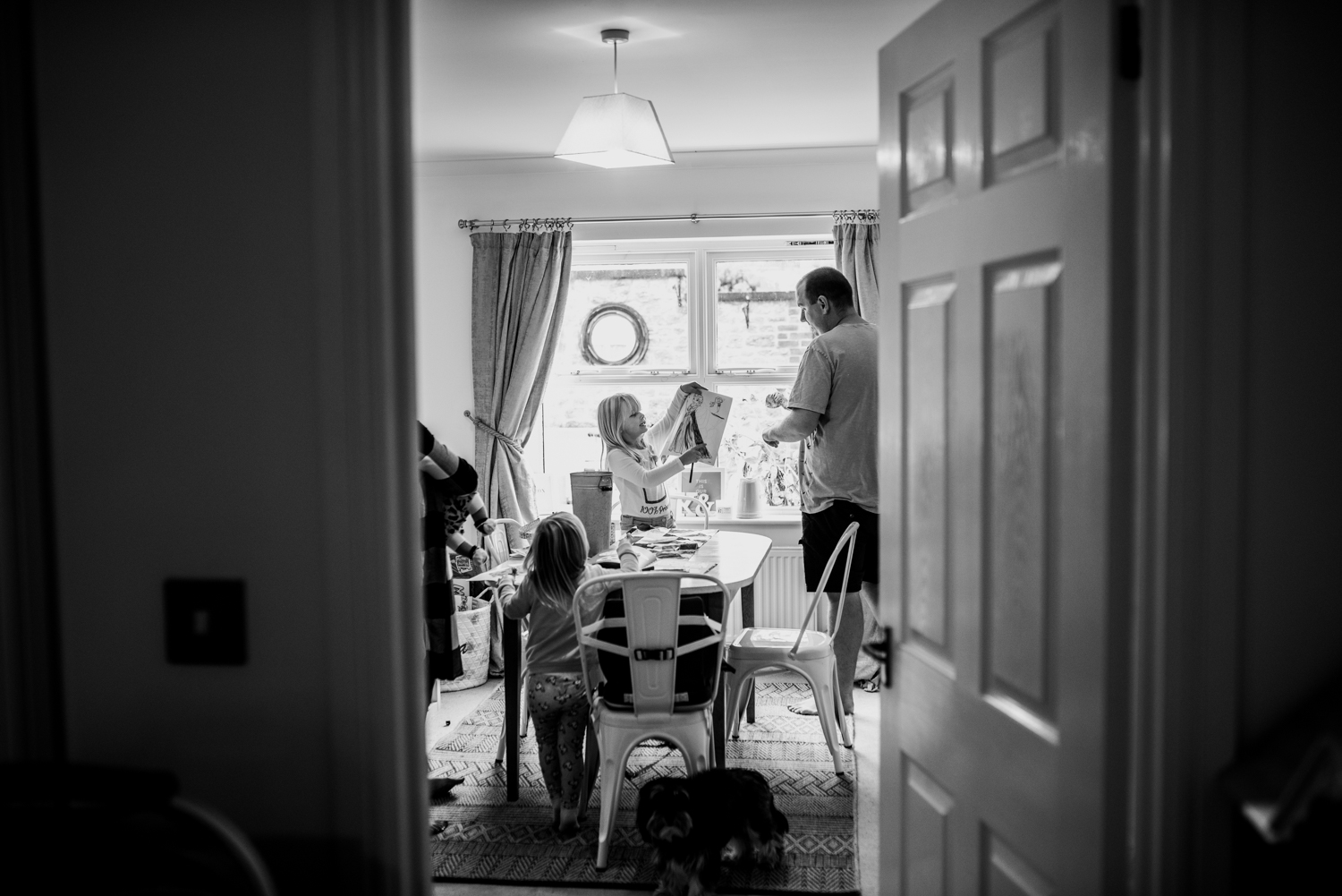 A shot through a door frame of daughter showing her father a picture she has drawn during this relaxed at-home photo session in Somerset.