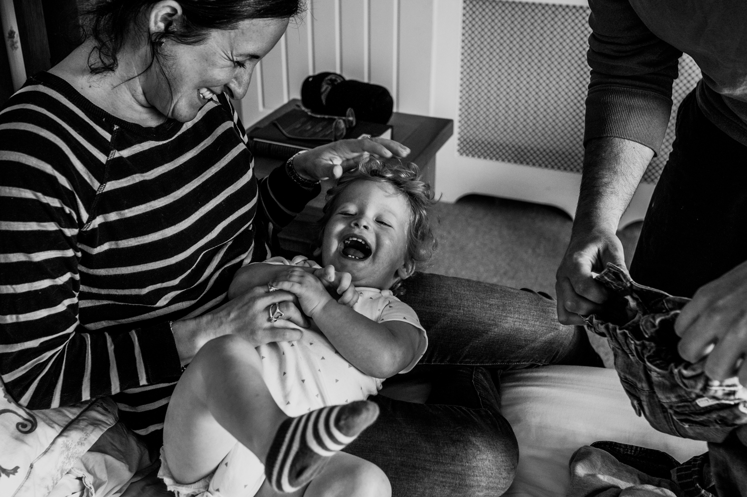 Mother tickles her toddler son on her lap whilst trying to get him dressed during in-home session in Chew Magna, Bristol.