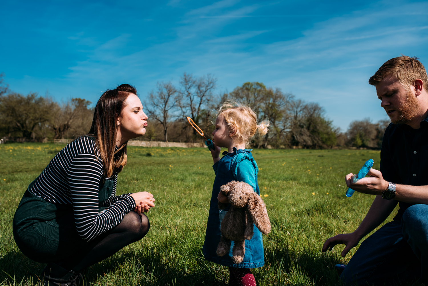 A little toddler girl blows bubbles in a meadow in Somerset sitting next to her two parents during this relaxed, unposed family photoshoot in Bath, Somerset.