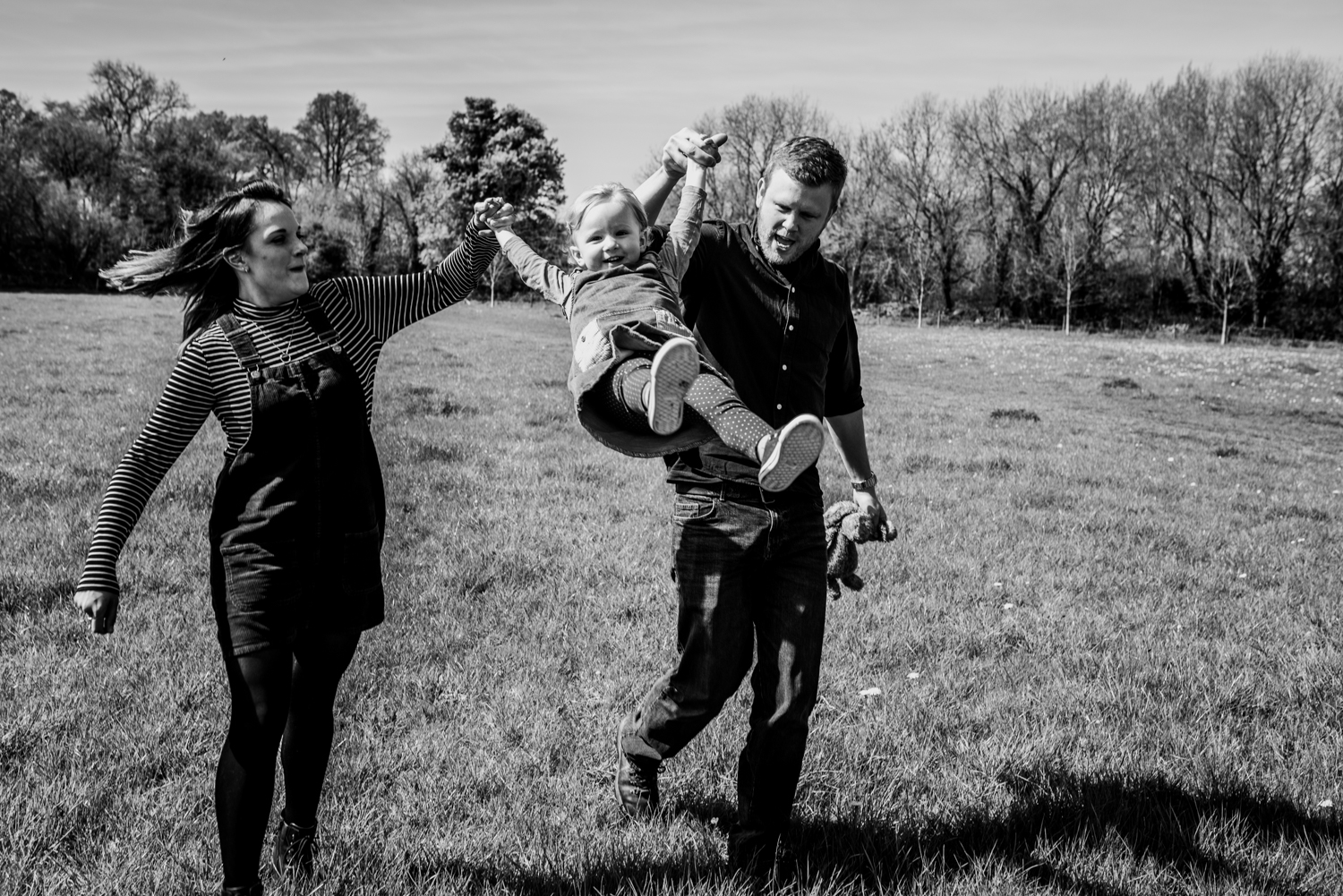 A little girl is swung high in the sky by her parents a sthey go on a walk in Somerset during this family natural outdoor photo shoot.