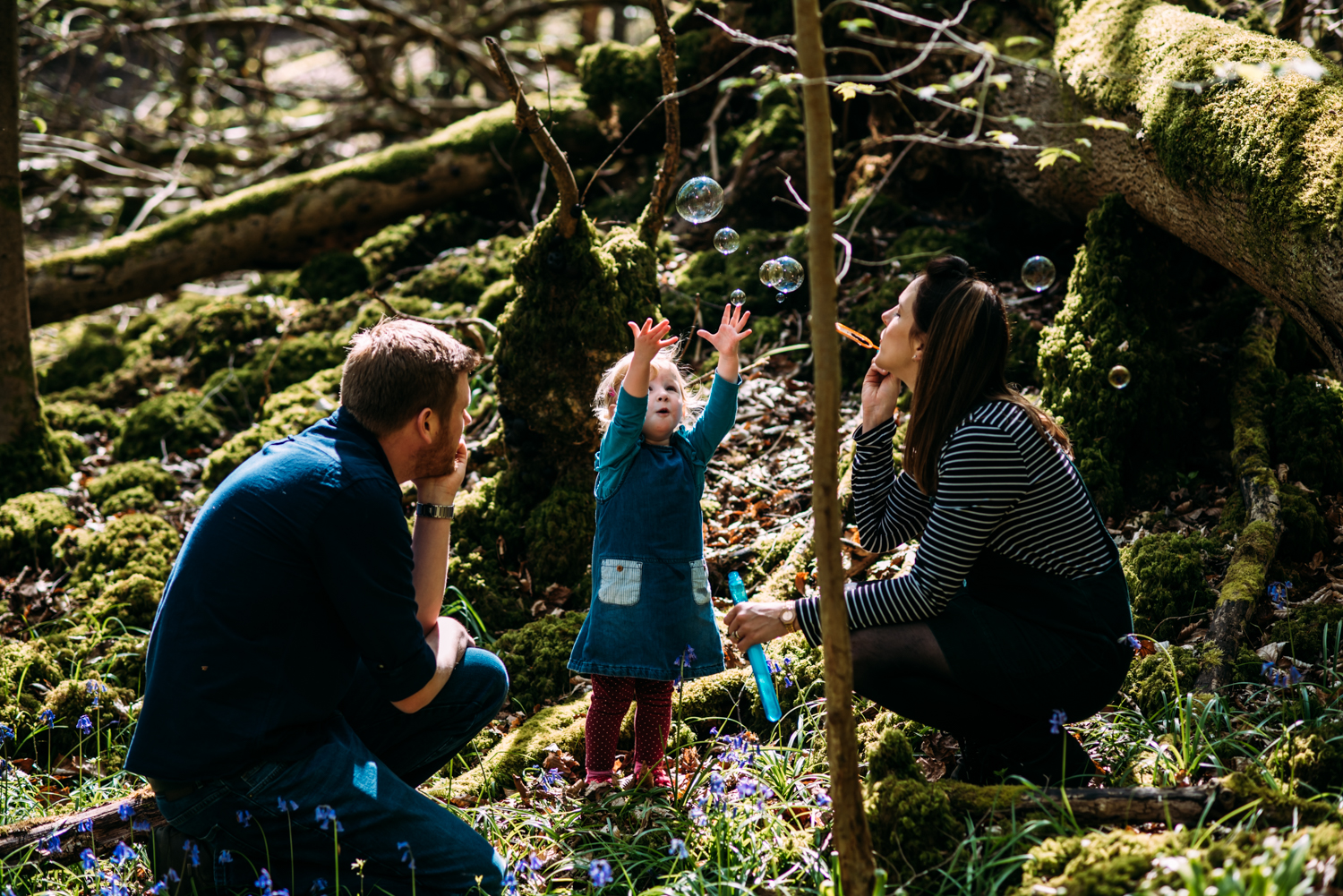 A little girl reaches up to touch bubbles her mother is blowing as the family sit amongs bluebells in a wood in Somerset for this relaxed, unposed family photoshoot in Bath, Somerset.