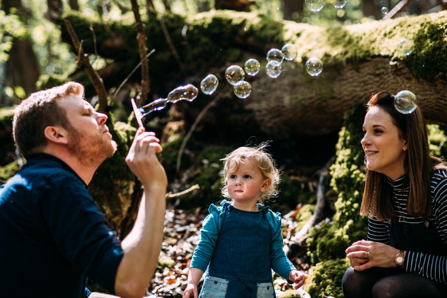 A family of three sit amongst bluebells blowing bubbles in a beautiful outdoor setting for this relaxed, unposed family photoshoot in Bath, Somerset.