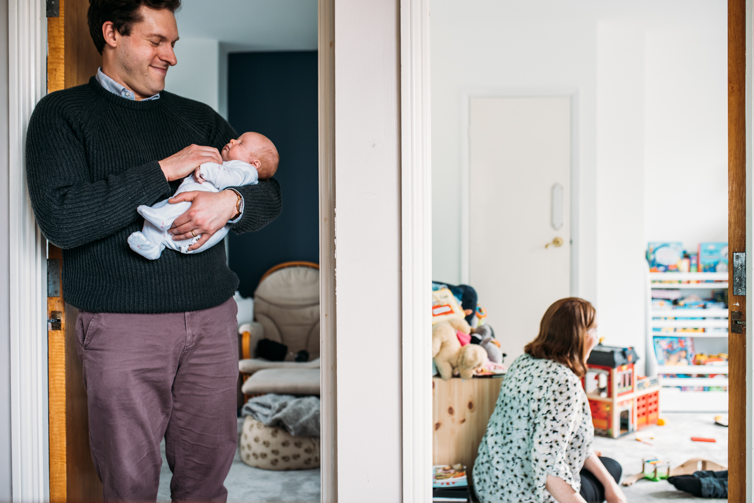 Shot through a doorway of a father holding his newborn daughter and a mother playong with her toddler son during this documentary family photo session in Bristol.