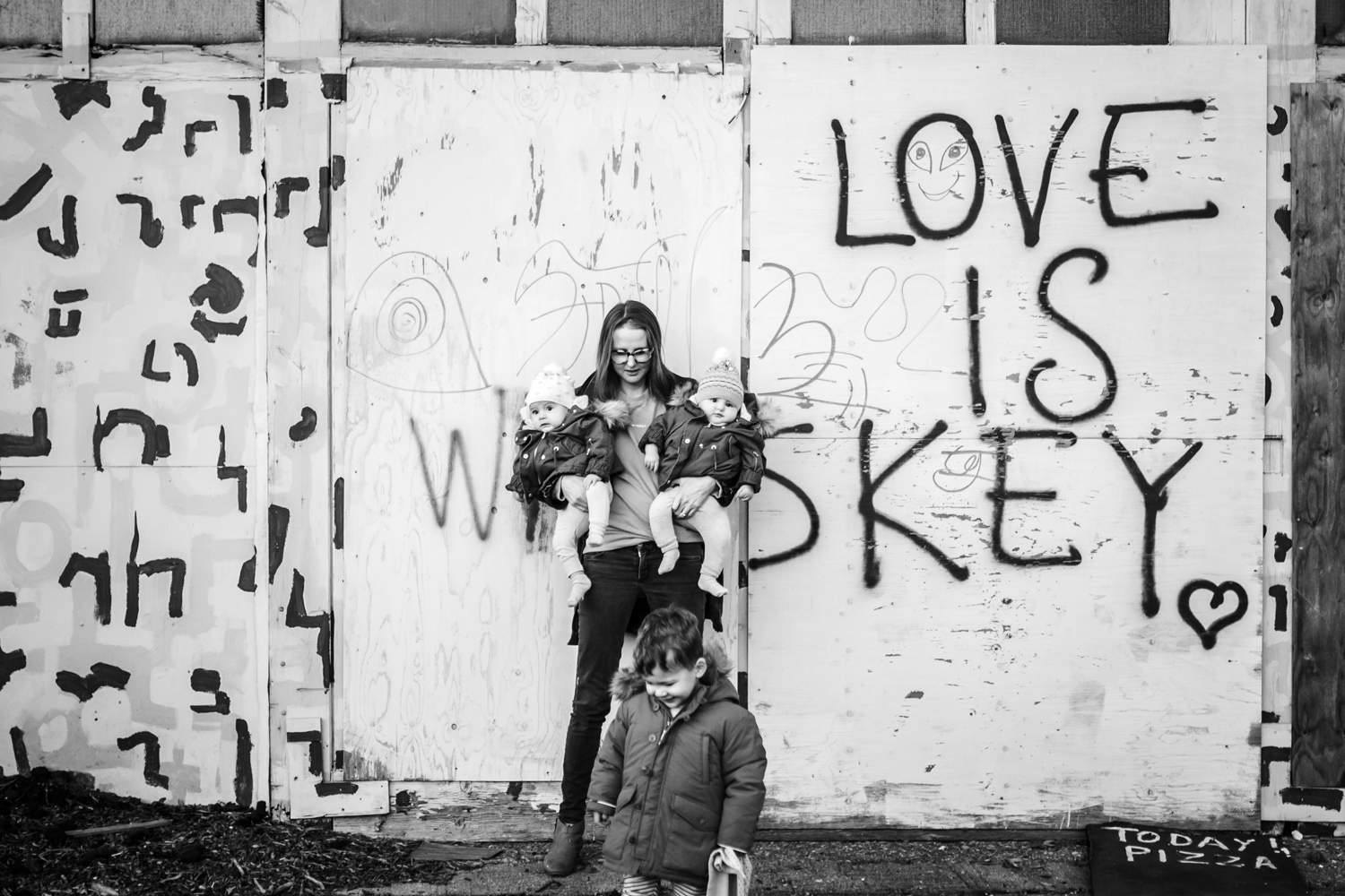 Mother stands agaisnt wall that says 'Love is Whiskey' holding her twin daughters as her two year old son runs in front of them during this documentary family photography session in Sussex UK.