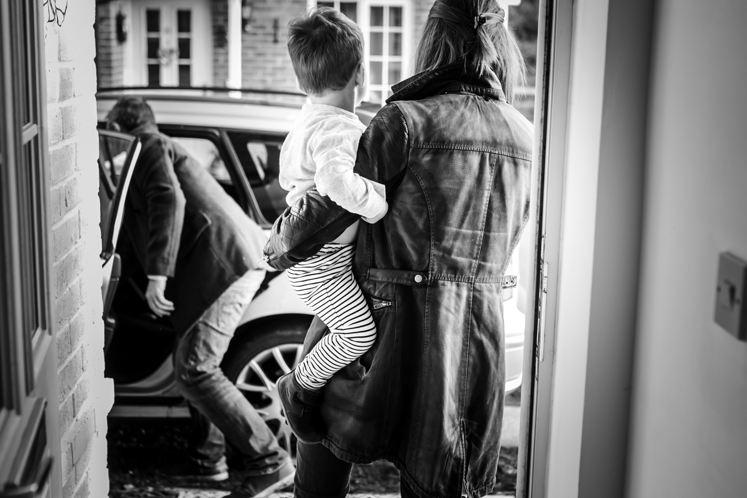 Mother holds son as she walks out of the door to their car during documentary family photography session in Sussex UK.