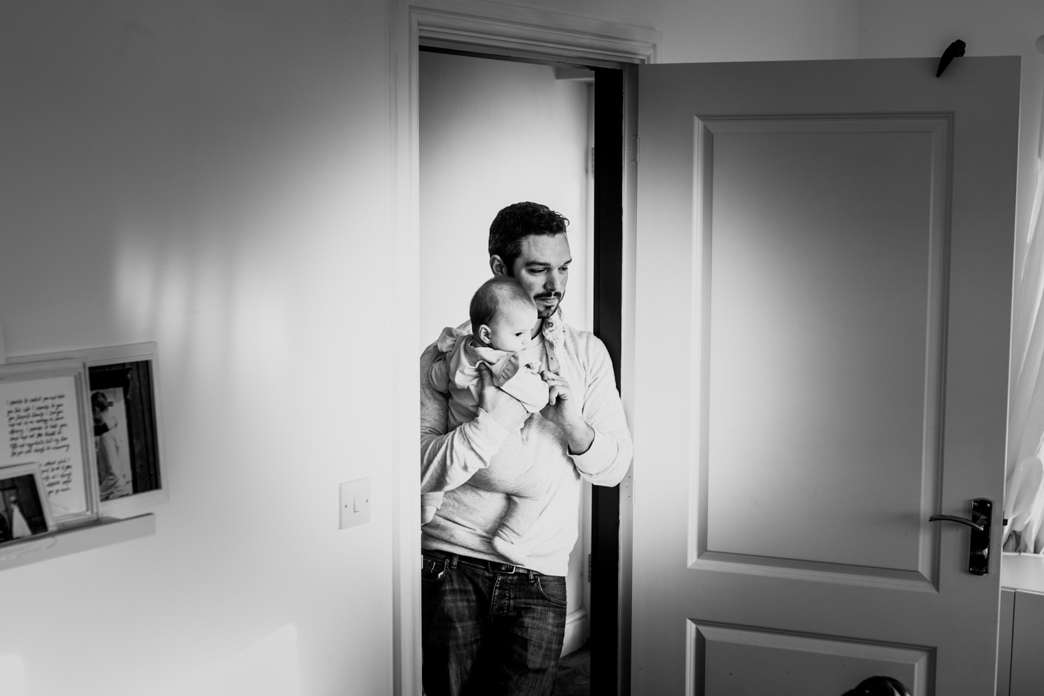 Father stands in doorway holding his baby daughter during this documentary family photography session in Sussex UK.