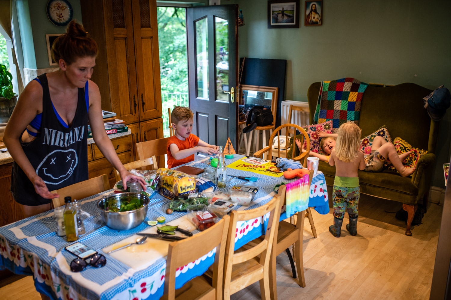 A mother and her three sons are all in their colourful kitchenn playing and preparing food during this unposed family portrait photography session.