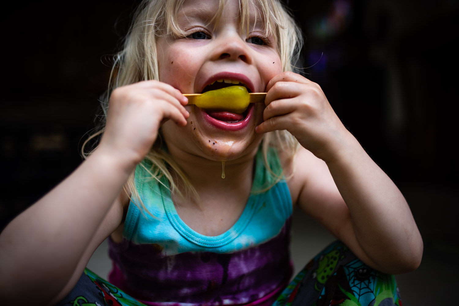 A little toddler boy sits licking an ice lolly during this fun, relaxed, unposed family photo shoot.